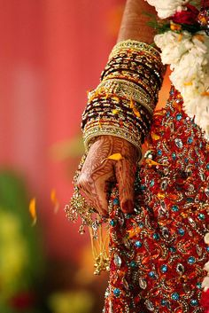 Close up of a woman's hand covered in mehndi at a wedding.