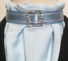 Euro style double bib. The crepe fabric drapes beautifully and is  easy care. Layered blue metallic grosgrain, silver metallic satin and blue satin ribbons. Square rhinestone slider.