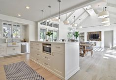 Open Floor Plan Kitchen and Family Room with Shiplap Wall and whitewashed hardwood floors. Redbud Custom Homes.