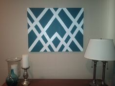 Modern DIY Wall Art. Paint a base color, tape off a design, and then paint on a top color and peel off the tape. Easy and cute!