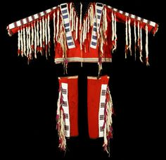 Blackfoot Shirt and Leggings decorated with panels of multicolored bead work and trimmed with ermine tails. Beaded strips trimmed with brass trade beads, all mounted on red wool Stroud cloth. Note the shirt is made with red Northern Wool Stroud cloth.