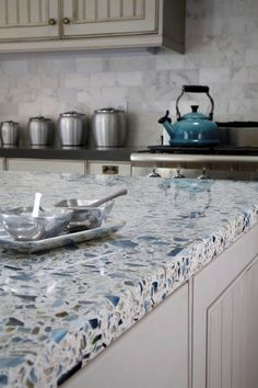 Kitchen ideas:  recycled glass countertops, bead board cabinets, and calacatta marble tile backsplash.