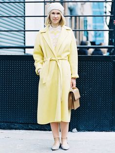 A printed sweater is layered over a collared shirt, paired with light pink trousers, finished off with a light yellow trench coat, ballet flats, a beanie, and a top-handle bag