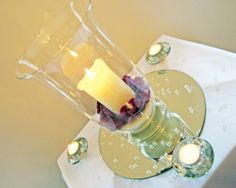 Hurricane Vase Centerpiece with sand, candles and purple petals.