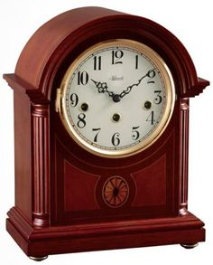 "Elegant Barrister style mantle clock made from select hardwoods and veneers in a rich mahogany finish. The front panel features fluted columns and exquisite inlaid marquetry. Brass 8-day key wound movement plays 4/4 westminster chimes.  Measures: H 11 5/8"" x W 9 1/4"" x D 5 1/8""   Three year manufacturer's warranty   Free shipping within the contiguous United States"