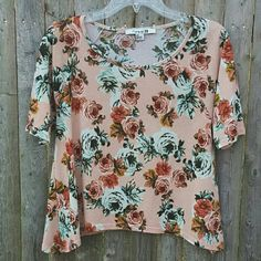 """Short Sleeve Floral Asymmetrical Cropped Blouse This cute floral blouse is perfect for the warmer weather ! It is cropped with a flowy asymmetric cut. Side lengths are 22"""", shortest length is 19"""". The color is rose pink, and the floral pattern have stone blue and rosewood pink roses ! Great preloved condition. Forever 21 Tops Crop Tops"""
