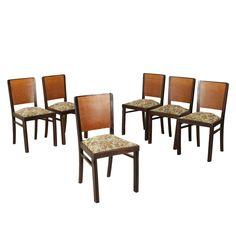 Gruppo di quattro sedie; legno tinto ebano e impiallacciatura di radica, imbottitura a molle, rivestimento in tessuto.