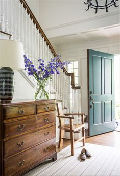 Love the beautiful teal blue front door and blue delphiniums on the antique chest of drawers!