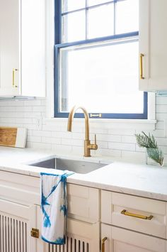 All white kitchen with pops of blue and gold fixtures