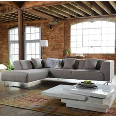 A soft curve shape sits on inverted sledge style legs creating a modern looking designer corner sofa. The solid wood frame is covered in a durable polyester fabric in a contemporary shade of grey.  The legs are smart chrome tubing. The three loose cushions have removable covers.