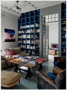 personally i'd prefer a duskier blue then the cerulean blue in the book shelves, but i love the balance of colors, white walls, high ceilings, rustic tables, leather, plush couch and window over the door. lovely lovely.