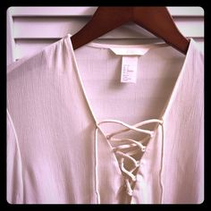 ✨PRICE DROP✨ Gauzy White Lace Up Top Gauzy White Lace Up Top. Basically brand new. Only worn to try it on. Very small black dot stain on inside of tie on one of the sleeves (I think this was already there when I bought it and never noticed). Not noticeable when on. Somewhat sheer material. Cute ties on sleeves and waist! H&M Tops Blouses