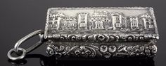 """A good William IV silver """"Castle Top"""" rectangular vinaigrette, the lid cast with a view of Windsor Castle within cast floral and leaf pattern borders, and with conforming bulbous sides and engine turned base, the gilt interior with finely pierced and engraved grille, 1.875ins x 1.25ins x .625ins high, by Nathanial Mills, Birmingham 1837 (weight 1.25ozs - with added suspension ring to left side)"""