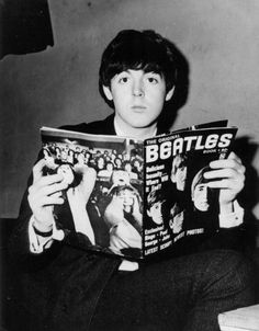 Paul McCartney poses for a portrait holding a Beatles fanzine which depicts 'Beatlemania' on the back cover, 1964.