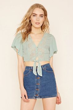Forever 21 Contemporary - A woven gauze crop top with short sleeves, a V-neckline with a buttoned front, a self-tie waist, and a semi-sheer floral crochet-paneled front and back. #thelatest