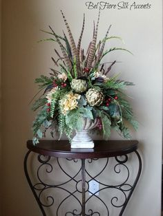 www.BelFioreSilkAccents.etsy.com This large arrangement contains cream hydrangea, dahlia, dried artichokes with pheasant feathers and berry accents. Would go with any décor with its neutral tones and can be viewed from all around. #TuscanArrangement #FeatherArrangement