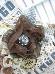 Fabric flower with paper leaves and jewel button center