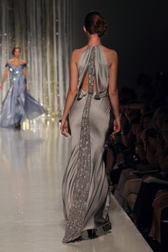 TONY WARD - Silver satin evening dress with a wrap over top. The back is highlighted by a band of rectangular stones.