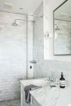 White on White Marble tile + traditional vanity + sleek porcelain light fixtures + exposed silver-dipped bulbs