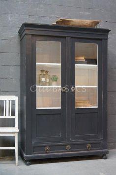 Vitrinekast 10016 - Prachtige oude vitrinekast, antraciet van kleur. De kast heeft stoere uitgewerkte slot plaatjes op de deuren en op de lade onderin. De binnenkant is wit van kleur, er zitten drie legplanken.