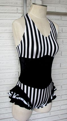 The black and white vertical stripe aerial costume is made to look like a ruffled leotard with corset over the top. The print is spandex with black stretch velvet corset. It features a v-ed halter top, high back coverage, and boy cut legs. The spa...