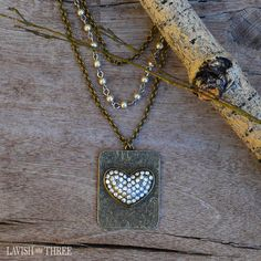 A trio of romantic chains make known the sweet romance of love. A pair of antique brass chains come alongside a petite strand of candlelight pearls set on silver. The vintage-inspired dog tag displays a beautiful clear crystal heart.