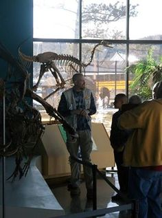 Tour guide Eric Goderis shows visitors a display featuring three Dromaeosaurus attacking a Pachycephalosaurus on a sunny Thursday in February. The skeletons were built at the museum by Dave Martin and Rob Housby.