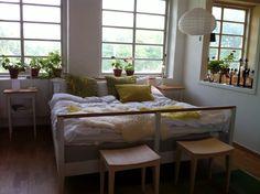 Säng norrgavel med vita linnelakan och gulgröna kuddar