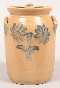 "Sold $ 350 Harrisburg, PA Daisy Decorated 1 Gallon Stoneware Jar. Circa. 1860-1880. Cobalt blue slip with central bell flower flanked by daisies and leaf design. Ovoid form with flared rim and applied ear handles. 10 1/4"" high with lid. Condition: Good with a couple of small chips and 1"" hairline."