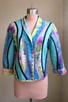 Curved shapes of linen, cotton and rayon fabrics are separated by bias tape to create this fabric collage jacket.