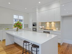Handless kitchen interior with sharp edges for a trendy and clean appearance. Gas stove top and silver kitchen appliances. Polished gloss white kitchen island bench top with seating area on the long side.
