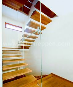 floating stair in stairwell, wood treads, glass railing http://www.sillertreppen.com/en/siller-stairs/