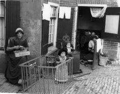 Afbeelding van twee vrouwen tijdens de voorbereidingen voor het eten met kinderen in een kinderstoel (kakstoel) en box, in klederdracht, te Spakenburg (gemeente Bunschoten). 1942 #Utrecht #Spakenburg