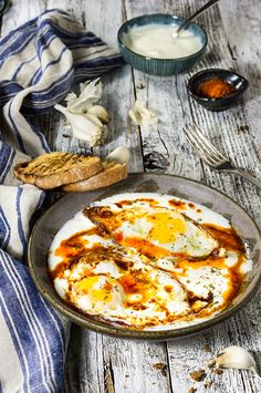 Eggs in garlicky yogurt - crispy fried egg whites and soft yolks, drizzled with butter paprika sauce, and served over a bed of cold, creamy garlicky yogurt - this is the ultimate egg dish to dig in with a piece of toasted bread! | www.viktoriastable.com
