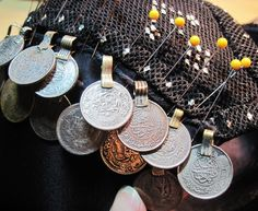 "Quickly stitch on a row of coins to a bra.  Coins with loop tops, can be strung onto a cord.  Distribute the coins using pins to space them to your taste.  Then hand sew the cord to the bra, being sure to make loops on either side of each coin to prevent them from sliding out of place.  This method will be in my upcoming book ""The Cloth of Egypt: All About Assiut"" with detail photos and descriptions.  By Dawn Devine ~ Davina -  www.davina.us"