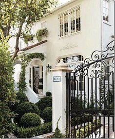 Clipped boxwood, vine or garland, black door, curly iron, white stucco ... gorgeous.