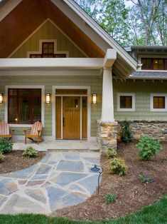 A sustainable Craftsman exterior with architectural details like tapered front columns showcases a modern take on the Arts and Crafts style. HardieShingle siding covers the body of the house, which is painted in Sherwin-Williams' Renwick Olive hue, while a stone walkway completes the classic Craftsman look for this home.