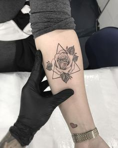 This flower head placed over a triangle is sweet and simple. Click through for more tattoo inspiration at CafeMom. #tattooideas #tattoos