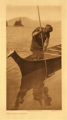 """On the west coast of Vancouver Island, 1915. """"The fisherman is taking flounders and other flatfish, which lie half-covered in the sand. It is frequently assumed that the prows of North Coast canoes are carved in imitation of a dog's head, but the natives deny any intentional resemblance. The notch in the top of the prow, dividing it into two sections suggestive of an animal's ears, is simply a rest for the shaft of a spear or harpoon."""""""