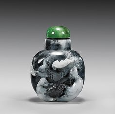 CARVED BLACK  GRAY JADE SNUFF BOTTLE 灰黑玉雕人物紋鼻煙壺 Finely hollowed and carved, Suzhou School-style carved black and gray jade snuff bottle; of thick rounded square form, the front with sage and attendant holding a barrel, with a bat overhead, the verso with typical landscape; green hardstone stopper; H: 2 3/4""