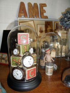 Composition sous cloche de verre, cubes en bois et cadrans de montre