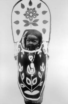 A Native American Flathead (Salish) baby is bound to a cradleboard with only its head showing. Flathead Indians, cradleboards 1907 :: Western History