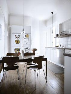 Kjøkken. Rundt det danske vintagespisebordet står fire meget spesielle Arne Jacobsen vintagestoler.  På de hvite skapdørene henger tegninger som Ted har laget. De forestiller Kung Fu-figurer.
