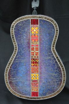 """A real guitar, hand painted and adorned with mirror, tempered glass, ball chain, stained glass, shell, millefiori, and ceramic tile. Measures  34.5"""" x 12"""" x 3.75"""""""