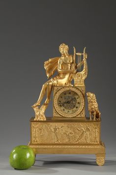 Charles X gilt bronze mantel clock featuring Apollo playing the lyre, a lion looking at him. He is sitting on the ormolu dial with Roman numerals for hours, finely chiseled...