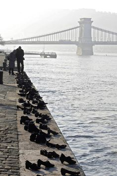 During WWII, Jews in Budapest were taken to the Danube River, ordered to remove their shoes & then were shot, falling into the water below. 60 pairs of iron shoes now line the river's bank, a ghostly memorial to the victims. 'Shoes on the Danube' by Can Togay and Gyula Pauer