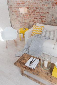 żółty stolik pomocniczy,poduszki z żółto-białym wzorem szerwonu,drewniany stolik vintage i ściana z cegły