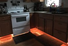 Mom sticks command hooks under her kitchen cabinet for a genius trick, with tube ;lighting (buy it on sale)