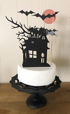 """Haunted house cupcake topper set for Halloween parties and events. Includes 11 toppers:-1 black glitter haunted house-1 orange glitter moon with bat-1 black crooked tree-8 black bats (different sizes)Cake size for topper size REFERENCE: 8.5"""" w and 3.25"""" h (height based from the bottom of the cake to the top) CAKE NOT INCLUDED Bolo Halloween, Halloween Birthday Cakes, Halloween Cupcake Toppers, Halloween Cups, Halloween Balloons, Halloween Garland, Pink Halloween, Halloween Party Supplies, Halloween Food For Party"""