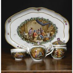 A Meissen porcelain part solitaire, circa 1760-70 painted with genre scenes after Teniers, comprising: a tray, 28.5 cm. wide; a small teapot and cover; a sugar bowl and cover; a cup; blue crossed swords and dot mark, inv. no. 4-1047 (6)